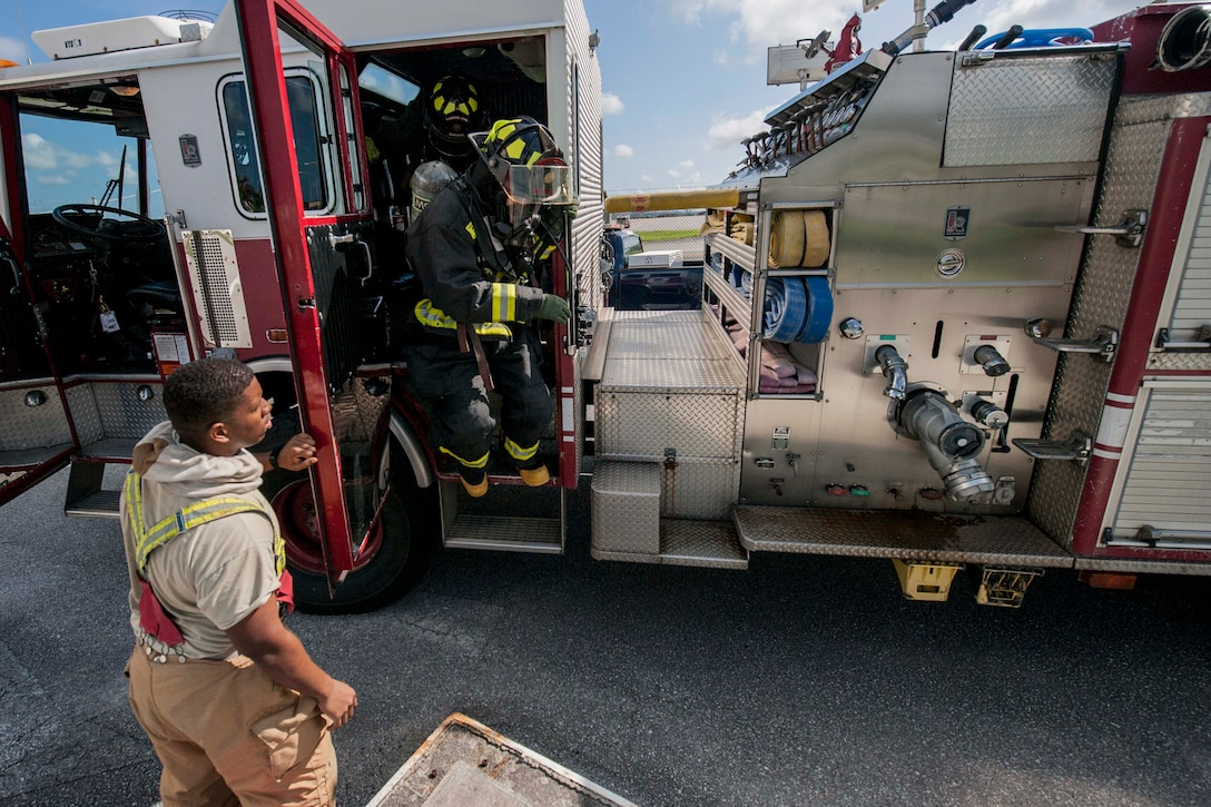 Firefighters from the 18th Civil Engineer Squadron exit a fire engine during a tower evacuation drill Aug. 15, 2016, at Kadena Air Base, Japan. Firefighters train on a regular basis in order to maintain constant readiness for emergencies. (U.S. Air Force photo by Senior Airman Peter Reft)