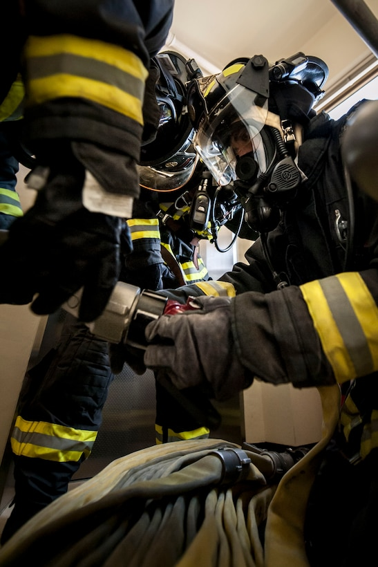 Yoshimi Sakurai, 18th Civil Engineer Squadron firefighter, connects hoses during a tower evacuation drill Aug. 15, 2016, at Kadena Air Base, Japan. The drill enabled firefighters to become familiar with fire and rescue procedures for the air traffic control tower. (U.S. Air Force photo by Senior Airman Peter Reft)