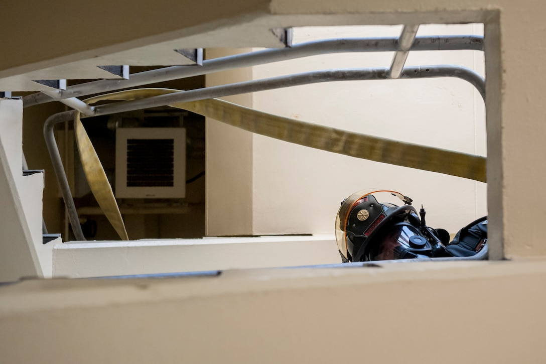 Senior Airman Brandon Hudson, 18th Civil Engineer Squadron firefighter, looks down a stairwell during a tower evacuation drill Aug. 15, 2016, at Kadena Air Base, Japan. Hudson and other firefighters of the 18th CES conduct fire and rescue exercises twice per week in order to remain ready day and night for possible emergencies. (U.S. Air Force photo by Senior Airman Peter Reft)