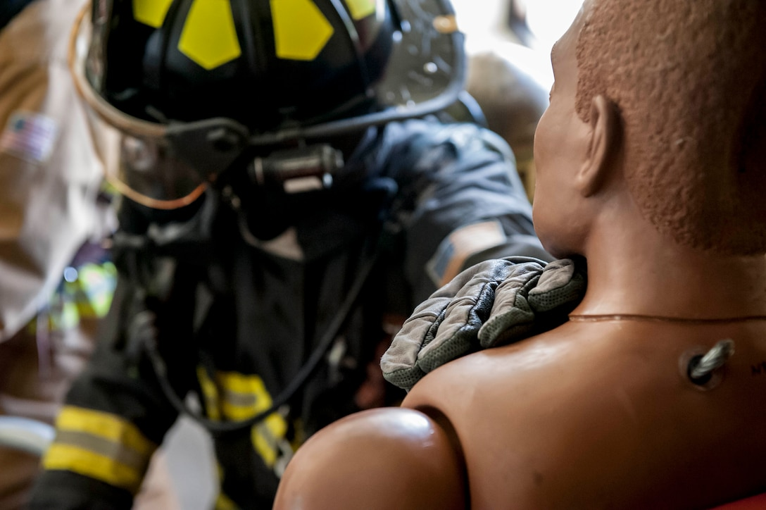 Staff Sgt. Demarcus Oliver, 18th Civil Engineer Squadron firefighter crew chief, supports a dummy during a tower evacuation drill Aug. 15, 2016, at Kadena Air Base, Japan. Training up to twice per week, firefighters ensure they remain constantly ready for possible emergencies, such as building evacuations and personnel recovery. (U.S. Air Force photo by Senior Airman Peter Reft)