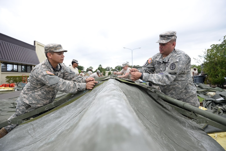 U.S. Army Spc. Dwight Chavez (left), 228th Combat Support Hospital preventive medicine specialist, and Sgt. Randy Sanchez (right), 228th CSH healthcare sergeant, construct a tent in support of a medical exercise being held at Misawa Air Base, Japan, Aug. 18, 2016. The 228th CSH will be conducting joint exercises over the course of a week with the 35th Medical Group from Misawa AB. (U.S. Air Force photo by Senior Airman Jarrod Vickers)
