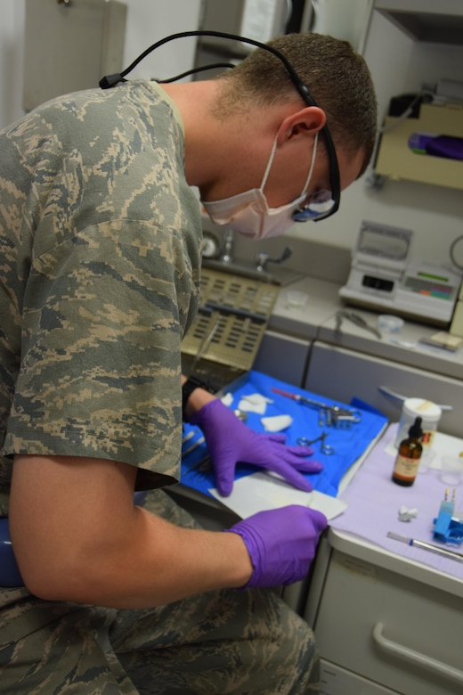 Sgt. Shane Hinton, 379th Expeditionary Medical Group dental technician,  mixes sealant for Maj. (Dr.) Benjamin Gantt to place inside a root canal on Senior Airman Jordan Thompson, 379th Expeditionary Logistics Readiness Squadron, July 30, 2016, Al Udeid Air Base, Qatar. The abundance of sugary energy drinks consumed here is a cause of tooth decay and dental visits according to Maj. Gantt. (U.S. Air Force photo/Technical Sgt. Carlos J. Treviño/Release)