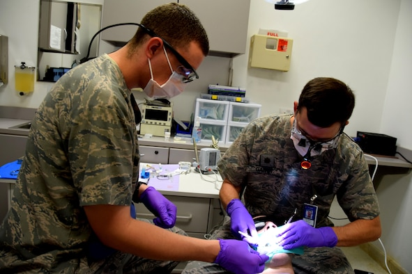 Dr. (Maj.) Benjamin Gantt, 379th Expeditionary Medical Operations Squadron dentist, adjusts a handheld mirror during a root canal procedure on Senior Airman Jordan Thompson, 379th Expeditionary Logistics Readiness Squadron fuels and cryogenics operator, July 30, 2016, at Al Udeid Air Base, Qatar. The dental clinic treats all service members and coalition partners stationed here and at Camp As Sayliyah, to include permanent party members and their families assigned here through the Command Sponsorship Program. (U.S. Air Force photo/Technical Sgt. Carlos J. Treviño/Released)
