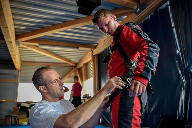 A skydiving instructor prepares a harness for Airman 1st Class Rocco Guanella, 435th Contingency Response Squadron member, before a tandem jump over Wallerfangen, Germany, Aug. 13, 2016. Comprehensive Airman Fitness is paramount in ensuring members are mission ready at all times. Fifteen Airmen received the opportunity to skydive to build on the spiritual foundation that keeps them prepared. (U.S. Air Force photo/Senior Airman Nicole Keim)