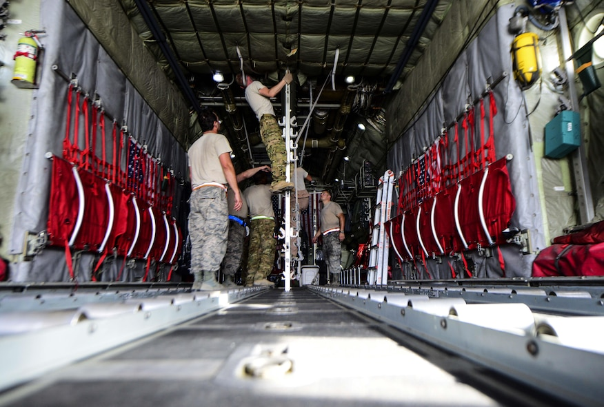 Airmen from the 746th Expeditionary Airlift Squadron and 746th Expeditionary Aircraft Maintenance Unit set up the C-130 Hercules prior to cargo and passengers arriving July 28, 2016, at Al Udeid Air Base, Qatar. The aeromedical equipment team along with the aeromedical evacuation operations team configures the aircraft prior to every mission by setting up the stations and dropping the straps for incoming patients and equipment to be stored during the flight. (U.S. Air Force photo/Senior Airman Janelle Patiño/Released)