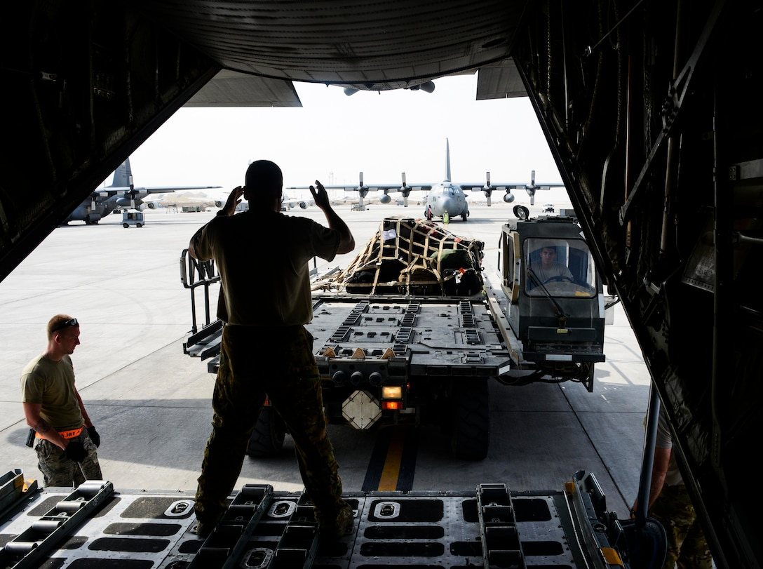 Master Sgt. Maurice Shivers, 746th Expeditionary Airlift Squadron loadmaster, marshals a K-Loader vehicle in preparation of loading equipment into a C-130 Hercules June 28, 2016, at Al Udeid Air Base, Qatar. A total of 147 Airmen from the 914th Airlift Wing out of Niagara Falls Air Reserve Station, N.Y., are deployed here under the 746h EAS and 746th Expeditionary Aircraft Maintenance Unit to execute C-130 combat missions in support of Operation Inherent Resolve and Operation Freedom's Sentinel. (U.S. Air Force photo/Senior Airman Janelle Patiño/Released)