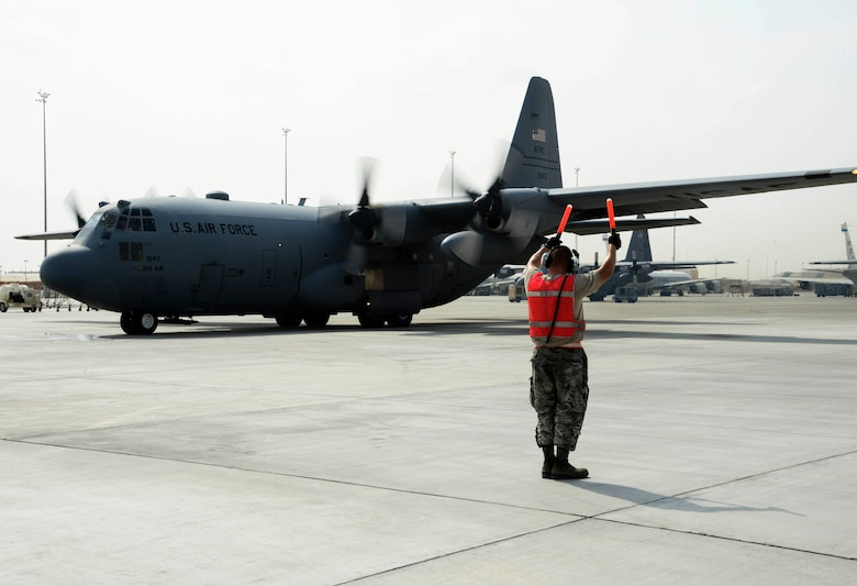 Senior Airman Steven Engels, 379th Expeditionary Aircraft Maintenance Squadron crew chief, marshals a C-130 Hercules on the flight line June 28, 2016, at Al Udeid Air Base, Qatar. Airmen from the 379th EAMXS are responsible for ensuring the aircraft are maintained to exact standards to support Operation Inherent Resolve and Operations Freedom's Sentinel. (U.S. Air Force photo/Senior Airman Janelle Patiño/Released)