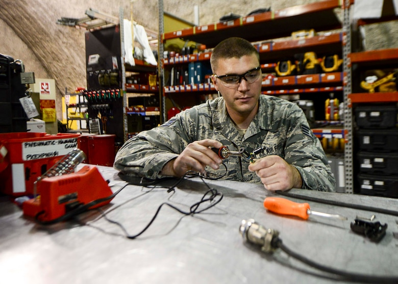 Staff Sgt. Taylor Elia, 379th Expeditionary Aircraft Maintenance Squadron communication navigation mission systems specialist, fixes a communication cord at the repair reference shop Aug. 12, 2016, at Al Udeid Air Base, Qatar. Airmen from the 379th EAMXS are responsible for ensuring the aircraft are maintained to exact standards to support Operation Inherent Resolve and Operations Freedom's Sentinel. (U.S. Air Force photo/Senior Airman Janelle Patiño/Released)
