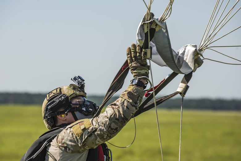U.S. Air Force Master Sgt. Christian Egger, 347th Rescue Group pararescueman, collects his parachute after landing from a high-altitude, low-opening jump, Aug. 18, 2016, at Moody Air Force Base, Ga. During operations at high altitudes, crewmembers are required to breathe 100 percent pure oxygen to combat the lowered oxygen levels present. (U.S. Air Force photo by Airman 1st Class Daniel Snider)