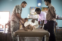 Maj. Nathan Shepard, a 673rd Medical Operations Squadron physical therapist, examines a Sri Lankan patient while being assisted by a translator during Pacific Angel 16-3 in Jaffna, Sri Lanka, Aug. 15, 2016. The exercise helped multilateral militaries in the Pacific improve and build relationships across a wide spectrum of civic operations, which bolster each nation's capacity to respond and support future humanitarian assistance and disaster relief operations. (U.S. Air Force photo/Senior Airman Brittany A. Chase)