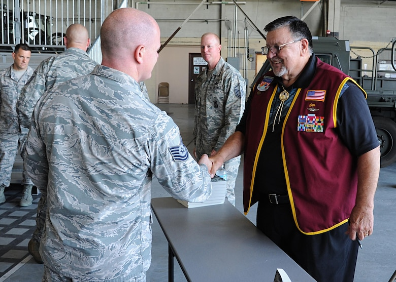 """Tech. Sgt. Daniel Cary, 319th Contracting Flight contracting officer, shakes hands with Capt. William """"Bill"""" Robinson, United States Air Force retired, August 18, 2016, on Grand Forks Air Force Base, N.D. Robinson signed copies of his book after speaking with Airmen about his time spent as a POW. (U.S. Air Force photo by Senior Airman Ryan Sparks/Released)"""