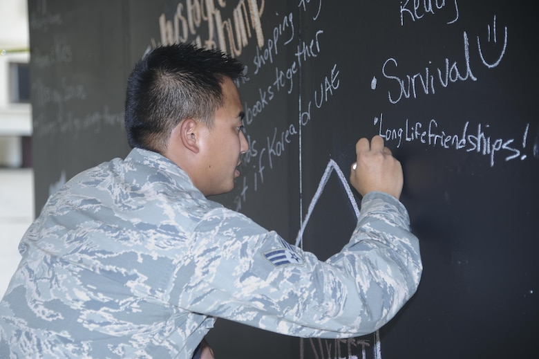 Senior Airman Timothy V. Bui, 12th Aircraft Maintenance Unit avionics specialist, writes on a chalkboard Aug. 17, 2016, at Beale Air Force Base, California. The chalkboard was part of a resiliency day event for participants to write and share their deployment experiences. (U.S. Air Force photo by Senior Airman Tara R. Abrahams)