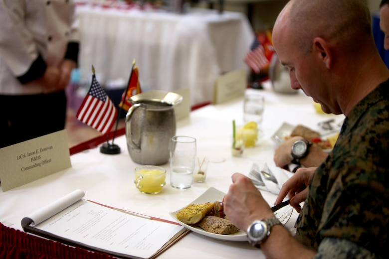 Lt. Col. Jason Donovan tastes Sgt. Megan McGuire's main entree during the Headquarters and Headquarters Squadron's Chef of the Quarter Competition aboard Marine Corps Air Station Cherry Point, N.C., Aug. 18, 2016. The quarterly competition tests food service specialists on the taste of their food, plate display, table appearance and culinary knowledge based on the anniversary theme they were given. Donovan, a judge during the competition, is the commanding officer for H&HS and McGuire is a food service specialist with H&HS. (U.S. Marine Corps photo by Cpl. Jason Jimenez/Released)