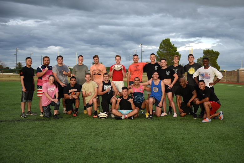 Rugby club members pose on the base softball field on Goodfellow Air Force Base, Texas, Aug. 17, 2016. The club includes permanent party, and students from multiple branches of service and even civilians from Angelo State University. (U.S.  Air Force photo by Airman 1st Class Caelynn Ferguson/Released)