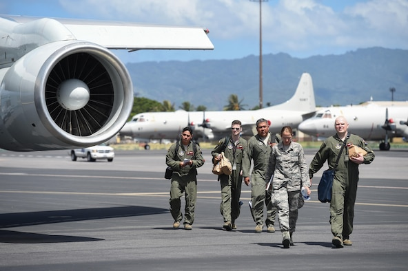 Reservists assigned to the 513th Air Control Group, walk by an E-3 Sentry wing July 25, 2016, at Joint Base Pearl Harbor-Hickam, Hawaii. More than 125 Airmen from the 513th Air Control Group and 552nd Air Control Wing are deployed to Hawaii in support of the Rim of the Pacific 2016 exercise. Twenty-six nations, more than 40 ships and submarines, more than 200 aircraft and 25,000 personnel are participating in RIMPAC from June 30 to Aug. 4, in and around the Hawaiian Islands and Southern California. The world's largest international maritime exercise, RIMPAC provides a unique training opportunity that helps participants foster and sustain the cooperative relationships that are critical to ensuring the safety of sea lanes and security on the world's oceans. RIMPAC 2016 is the 25th exercise in the series that began in 1971. (U.S. Air Force photo by 2nd Lt. Caleb Wanzer)