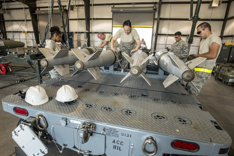 Airmen from the 325th Maintenance Squadron, Tyndall Air Force Base, Fla., strap GBU-32 bombs onto a trailer Aug. 2 at Hill AFB. The bombs were used during Combat Hammer, an exercise which took place at Hill AFB and the Utah Test and Training Range. (U.S. Air Force photo by Paul Holcomb)