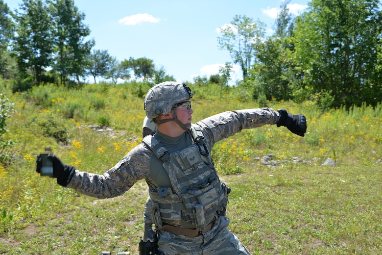 U.S. Air Force Senior Airman Brandan Able, with the 157th Security Forces Squadron, New Hampshire Air National Guard, throws a smoke grenade as part of skills training, Aug. 4, 2016, at the New Hampshire National Guard Training Site, Center Strafford, N.H.  (Air National Guard photo by Airman 1st Class Ashlyn J. Correia)