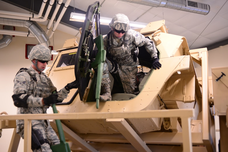 U.S. Airman 1st Class Connor Cranstron holds a door open for Airman 1st Class Dalton Briggs, both with the 157th Security Forces Squadron, New Hampshire Air National Guard, as he exits a Humvee rollover simulator during skills training, Aug. 4, 2016, at the New Hampshire National Guard Training Site, Center Strafford, N.H.(Air National Guard photo by Airman 1st Class Ashlyn J. Correia)