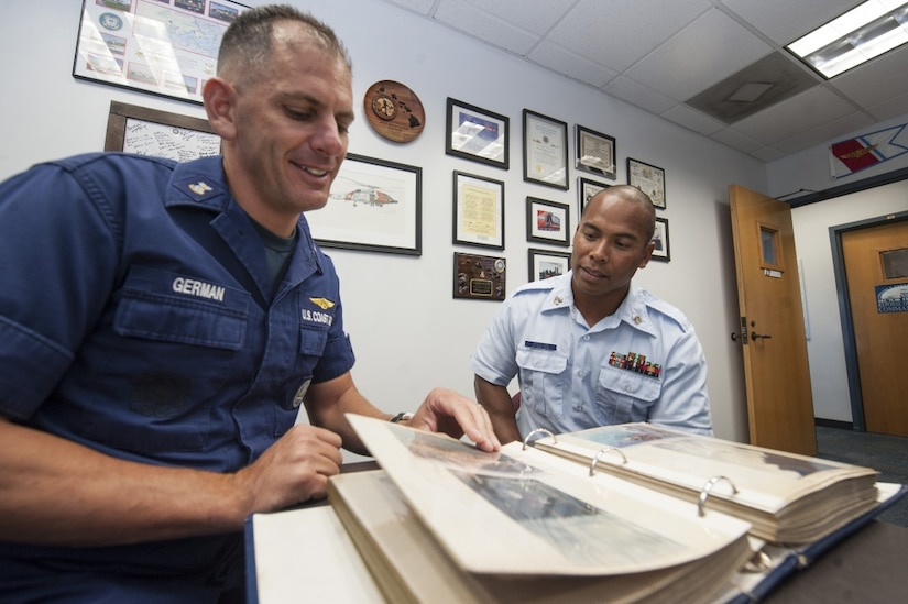 Coast Guard Command Master Chief Petty Officer Ronny German and Coast Guard Petty Officer 1st Class Kensley Raigeluw, look at old photos on Sand Island, Hawaii, Aug. 17, 2016. Raigeluw attributes the Coast Guard's visit to his island of Woleai more than 20 years ago for the reason he decided to serve. Air Force photo by Staff Sgt. Christopher Hubenthal