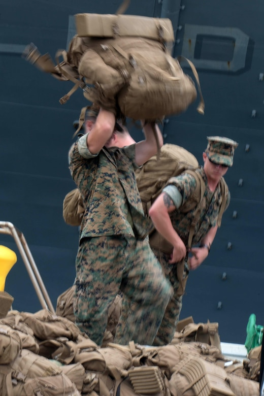 WHITE BEACH, Okinawa, Japan, (Aug. 20, 2016) – A Marine with the 31st Marine Expeditionary Unit, lifts his pack before going aboard the USS Bonhomme Richard (LHD-6), at White Beach, Okinawa, Japan, Aug. 20, 2016. The 31st MEU is embarked aboard the ships of the Bonhomme Richard Amphibious Ready Group during a regularly scheduled patrol of the Pacific region.