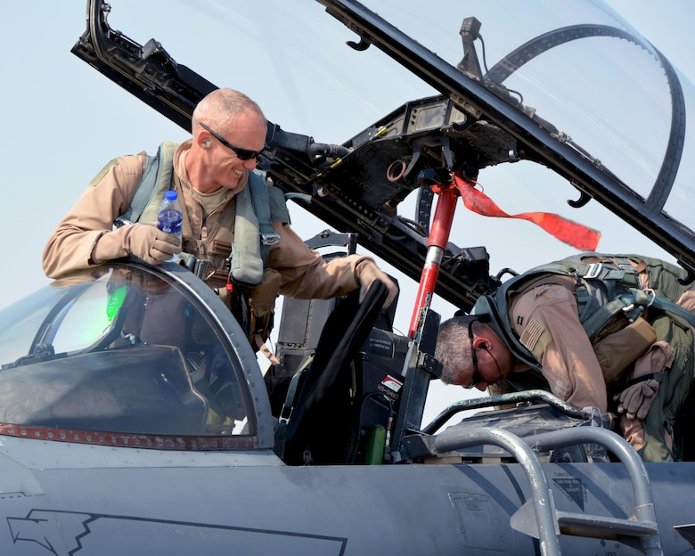 Lt. Col. Brandon, 335th Expeditionary Fighter Squadron commander, and Capt. Matthew, 335th Expeditionary Fighter Squadron weapon systems officer, prepare to disembark from F-15E Strike Eagle #89-0487 after a milestone flight at an undisclosed location, Aug. 16, 2016. The jet attained 12,000 flying hours and Brandon achieved 3,000 flying hours during the same flight. (U.S. Air Force photo by Staff Sgt. Samantha Mathison)