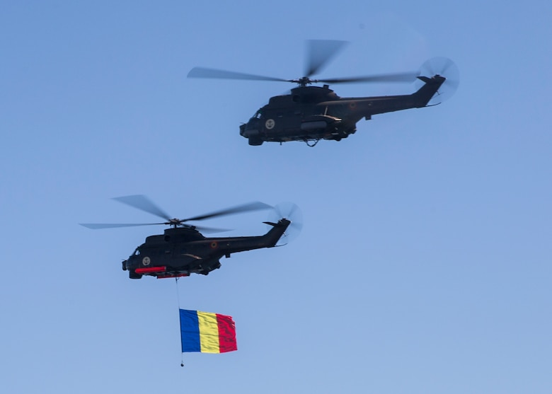Two Romanian helicopters fly over a delighted crowd of spectators while carrying the Romanian flag during the 114th annual Navy Day celebration at the Port of Constanţa, Romania, Aug. 15, 2016. U.S. Sailors and Marines supporting the Black Sea Rotational Force 16.2 helped pay tribute to the prestigious history of the Romanian navy and highlighted the military's movement toward new developments and modernizations. Black Sea Rotational Force is an annual multilateral security cooperation activity between the U.S. Marine Corps and partner nations in the Black Sea, Balkan and Caucasus regions designed to enhance participants' collective professional military capacity, promote regional stability and build enduring relationships with partner nations. (U.S. Marine Corps photo by Sgt. Michelle Reif)