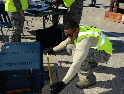 Staff Sgt. Allan Canizales, a mobility training instructor assigned to the 6th Logistics Readiness Squadron, weighs and measures cargo during a mobility exercise at MacDill Air Force Base, Fla., Aug. 16, 2016. Canizales was in charge of checking that all equipment being processed is documented with accurate size and weight measurements. (U.S. Air Force Photo by Airman 1st Class Rito Smith)