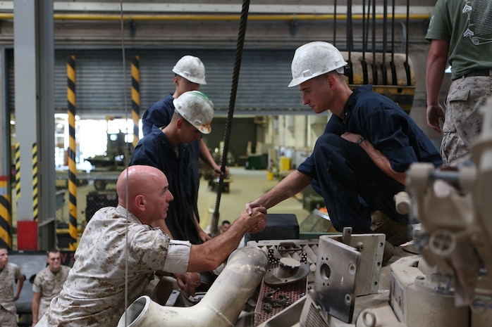 U.S. Marine Brig. Gen. David A. Ottignon greets and presents a challenge coin to Lance Cpl. Michael Hamilton, a tank mechanic from Combat Logistics Company 13, Combat Logistics Regiment 15, 1st Marine Logistics Group, at Marine Corps Air Ground Combat Center Twentynine Palms, Calif. Aug. 12, 2016. Ottignon is the 1st MLG commanding general. The MLG commanding general, sergeant major, and command master chief visited the combat center to speak with unit commanders as well as engage junior Marines and non-commissioned officers to get a sense of how MLG units are doing and what areas could be improved upon. (U.S. Marine Corps photo by Sgt. Carson Gramley/released)