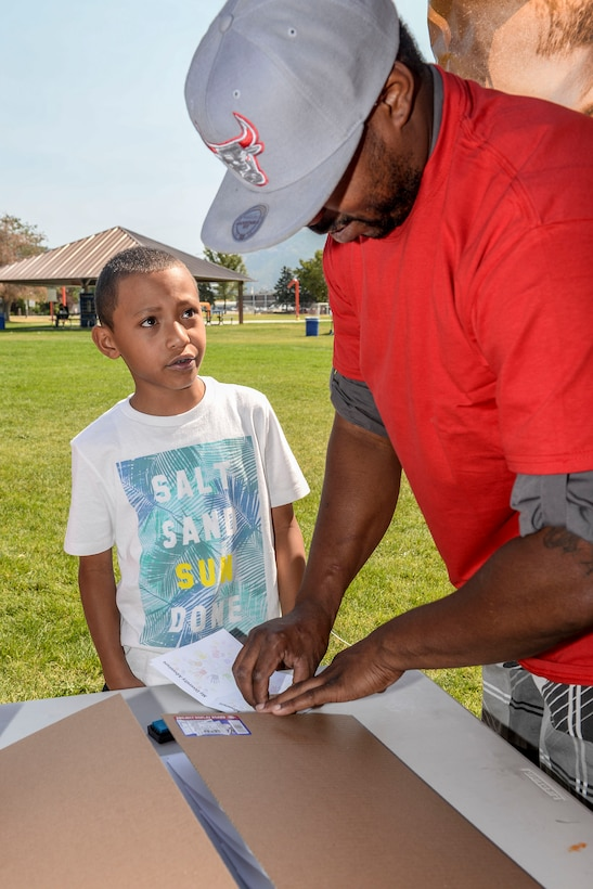 Staff Sgt. Deqoune Kennedy, 75th Logistics Readiness Squadron, stamps a 'passport' for 8-year-old Akoni Suafo'a during the Team Hill Diversity Festival August 20 at Centennial Park. Suafo'a is the son of Staff Sgt. Elenita Suafo'a, 388th Fighter Wing. The new Team Hill Diversity Council brought together representatives from all of Hill AFB's annual special observances to celebrate and provided information about the base's unique community and diversity. (U.S. Air Force photo by Paul Holcomb)