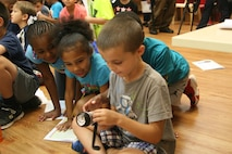 Children at the Quantico Youth Center examine a hand-cranked radio and flashlight, an example of the kind of tool they could keep in their personal pillowcase emergecy preparedness kits. The American Red Cross visited the facility August 8 to present the education session.