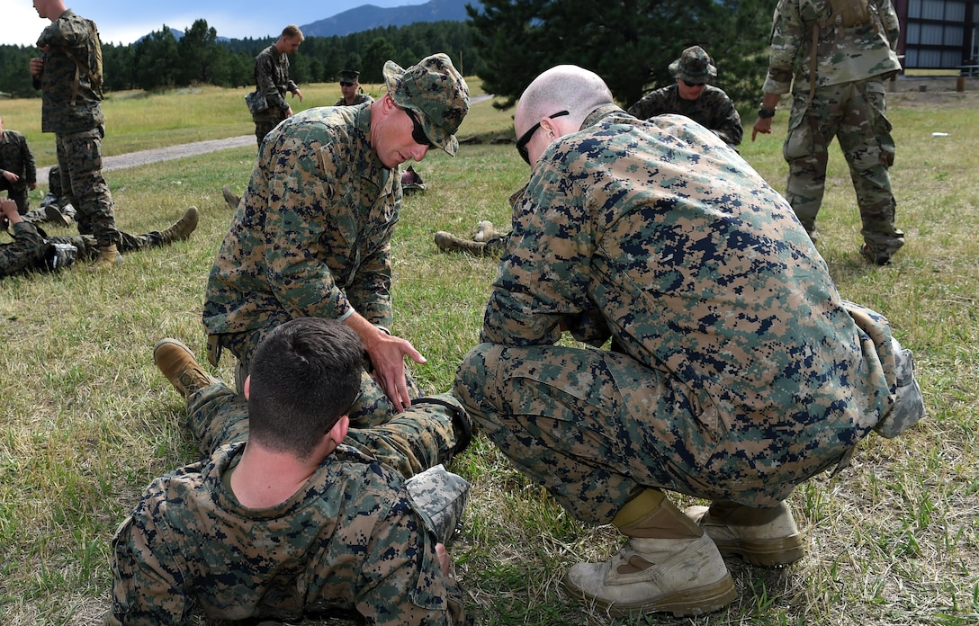U.S. Marine Master Sgt. Brian P. Geraghty, Company A, Marine Cryptologic Support Battalion senior enlisted Marine, explains the importance of proper tourniquet placement to his Marines during their summer training Aug. 17, 2016, at the U.S. Air Force Academy, Colo. Marines from the MCSB spent approximately two hours learning combat medicine skills from Senior Airman Ronnie Perez, 460th Medical Operations Squadron medical technician. (U.S. Air Force Photo by Airman Holden S. Faul/ Released)