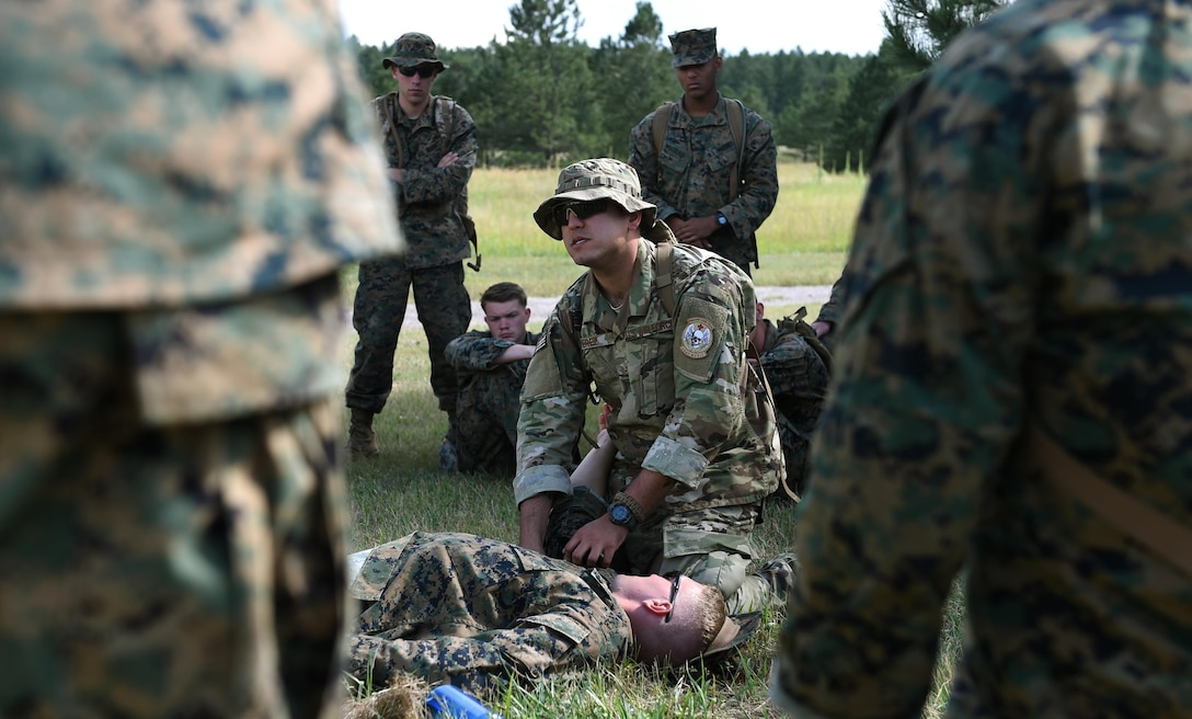 Senior Airman Ronnie Perez, 460th Medical Operations Squadron medical technician, instructs U.S. Marines, assigned to Company A, Marine Cryptologic Support Battalion, how to properly apply a tourniquet Aug 17, 2016, at the U.S. Air Force Academy, Colo. Perez volunteered to join the battalion for their summer field training to teach basic life-saving skills service members must know prior to being deployed. (U.S. Air Force photo by Airman Holden S. Faul/ Released)