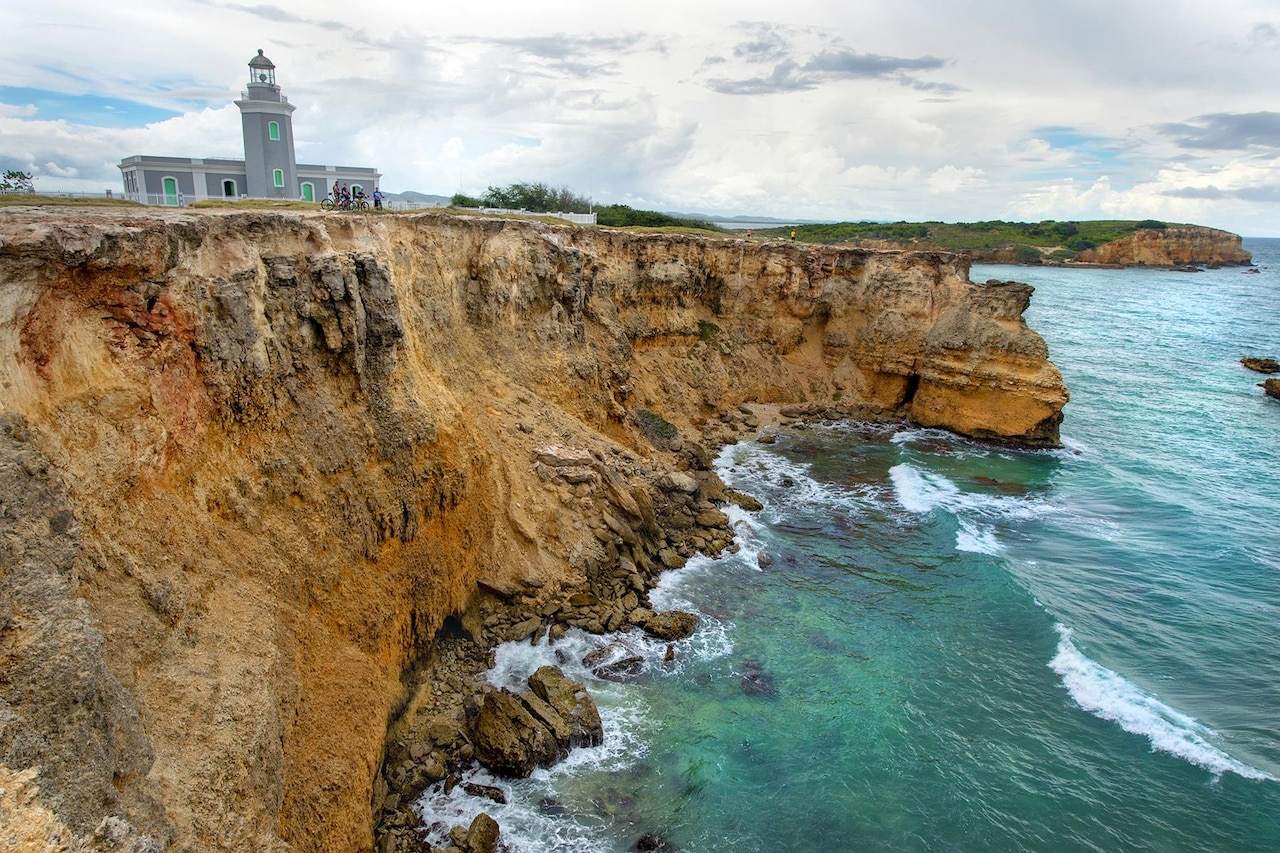 Veterans stand with their mountain bikes on a cliff overlooking the Caribbean Sea at the Cabo Rojo Lighthouse in Cabo Rojo, Puerto Rico, Aug. 13, 2016. The veterans rode with the Warriors 4 Life nonprofit veterans group, which helps veterans cope with physical and psychological wounds and creates healthy lifestyles for them and their families. DoD photo by EJ Hersom