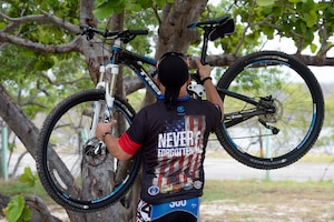 Iraqi Freedom veteran Army Master Sgt. David Camacho hangs a mountain bike on a tree in Cabo Rojo, Puerto Rico, Aug. 13, 2016. Camacho and other veterans rode with the Warriors 4 Life nonprofit veterans group, which helps veterans cope with physical and psychological wounds and creates healthy lifestyles for them and their families. DoD photo by EJ Hersom