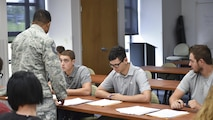 Master Sgt. Joseph Poltor, a Youngstown Air Reserve Station recruiter, guides Dan Madeline, Cross Scarpaci and Michael Amato through enlistment paperwork here, Aug. 19, 2016. The three new Airmen took the oath of enlistment surrounded by friends and family to begin their Air Force Reserve careers. Poltor recently made 150 percent of his recruitment quota, becoming the third Youngstown recruiter in recent history to reach the century club. (U.S. Air Force photo/Eric White)