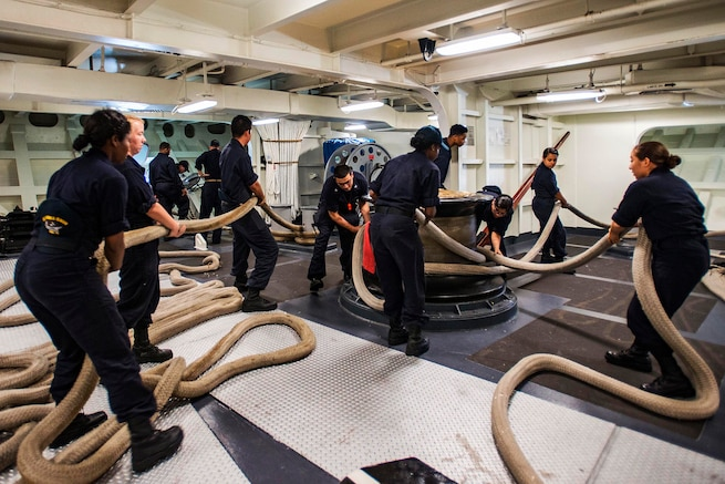 Sailors haul in mooring lines aboard the USS Ronald Reagan in Yokosuka, Japan, Aug. 18, 2016. The sailors arrange the lines in a side-by-side pattern to keep them from getting tangled in their legs. The Reagan provides a combat-ready force in the Indo-Asia-Pacific region. Navy photo by Seaman Jamaal Liddell