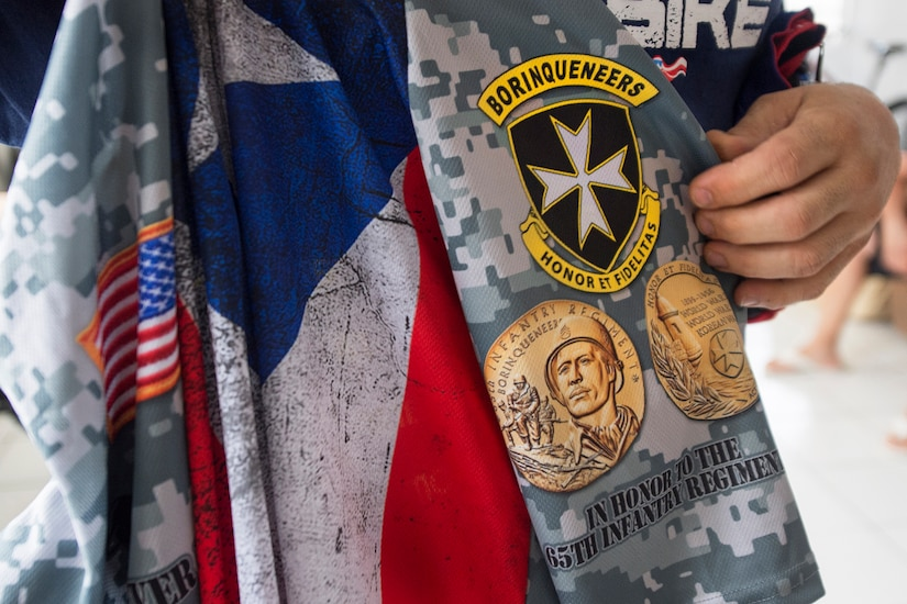 A veteran holds a bicycle jersey with an imprinted emblem of Puerto Rico's 65th Infantry Regiment in Cabo Rojo, Puerto Rico, Aug. 13, 2016. Veterans riding with the Warriors 4 Life nonprofit veterans group dedicated their ride in a 100-kilometer mountain bike race to the regiment famous for its bayonet charge in the Korean War. DoD photo by EJ Hersom