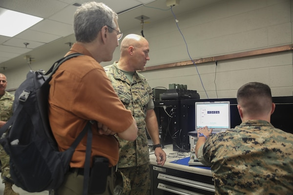 Alan Estevez, left, Principal Deputy under Secretary of Defense for Acquisition, Technology and Logistics, observes a Marine conduct electronic maintenance at Camp Lejeune, N.C., Aug. 17. Several distinguished visitors from the Department of Defense visited Camp Lejeune and the USNS Wright to observe technological innovation enhancing logistical capabilities throughout II Marine Expeditionary Force. (U.S. Marine Corps photo by Sgt. Lucas Hopkins)