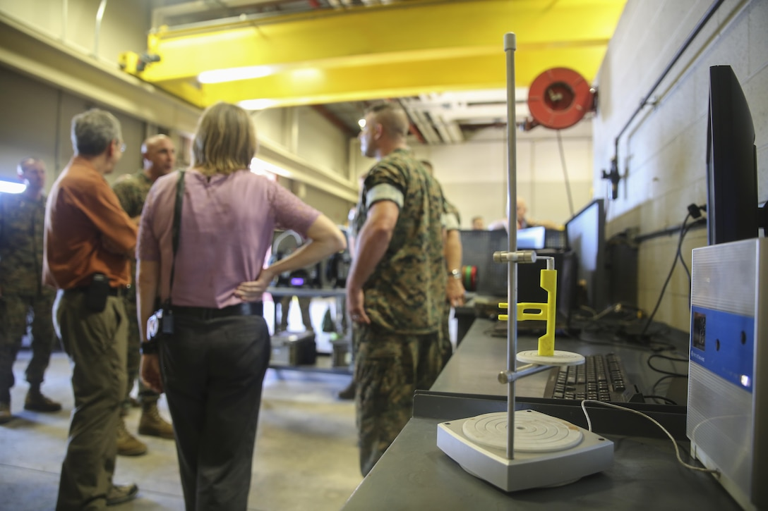 Distinguished visitors from the Department of Defense speak with Marines from 2nd Maintenance Battalion following a demonstration of 3D printing and additive manufacturing technology at Camp Lejeune, N.C., Aug. 17. Technological advancements such as 3D/AM printing has the potential to vastly reduce the time required to acquire small spare parts for vehicles and other equipment. Alan Estevez, Principal Deputy under Secretary of Defense for Acquisition, Technology and Logistics, Kristin French, Principal Deputy under Secretary of Defense for Logistics and Material readiness, and Lt. Gen. Michael Dana, Deputy Commandant of Installations and Logistics, visited the base to observe logistical innovation throughout II Marine Expeditionary Force. (U.S. Marine Corps photo by Sgt. Lucas Hopkins)
