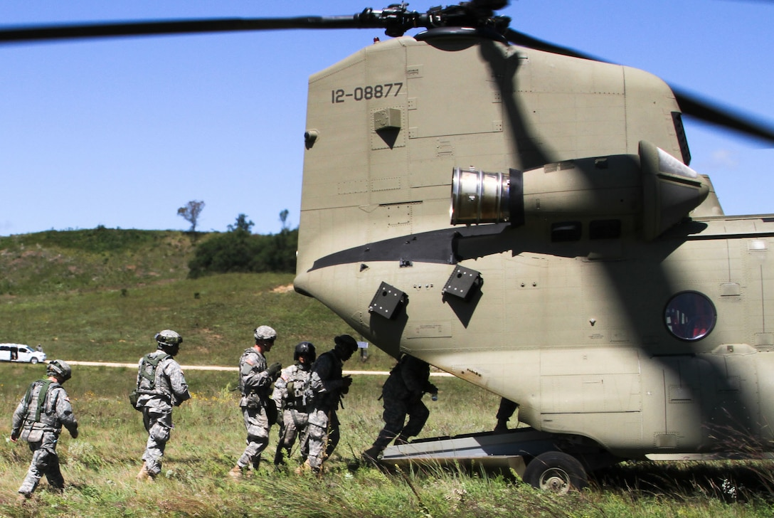 FORT MCCOY, Wis. -- Army Reserve Soldiers from the 824th Quartermaster Company out of Fort Bragg, N.C., proceed to board the rear cabin of the CH-47 Chinook as part of the Combat Support Training Exercise at Fort McCoy, Wis., on Aug. 17, 2016. CSTX immerses Army Reserve Soldiers and other service members in real-world training scenarios to enhance unit readiness in the planning, preparation, and execution of combat service support operations. (U.S. Army Reserve photo by Spc. Christopher A. Hernandez, 345th Public Affairs Detachment)