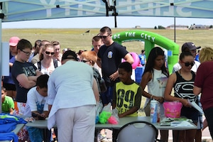 Participants fill out registration forms during Slide the City at Schriever Air Force Base, Colorado, Friday, Aug. 19, 2016. More than 370 people took at least one turn down the slide, with hundreds more in attendance during the 50th Force Support Squadron-sponsored event. (U.S. Air Force photo/Brian Hagberg)