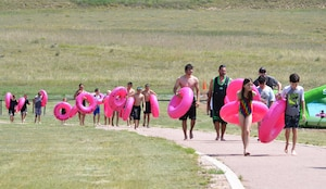 Sliders carry their tubes back up the hill following their trip down a giant slip-and-slide during Slide the City at Schriever Air Force Base, Colorado, Friday, Aug. 19, 2016. This year, the event was moved from the road next to the fitness center to a hill behind the facility to give participants a longer, steeper slide. (U.S. Air Force photo/Brian Hagberg)