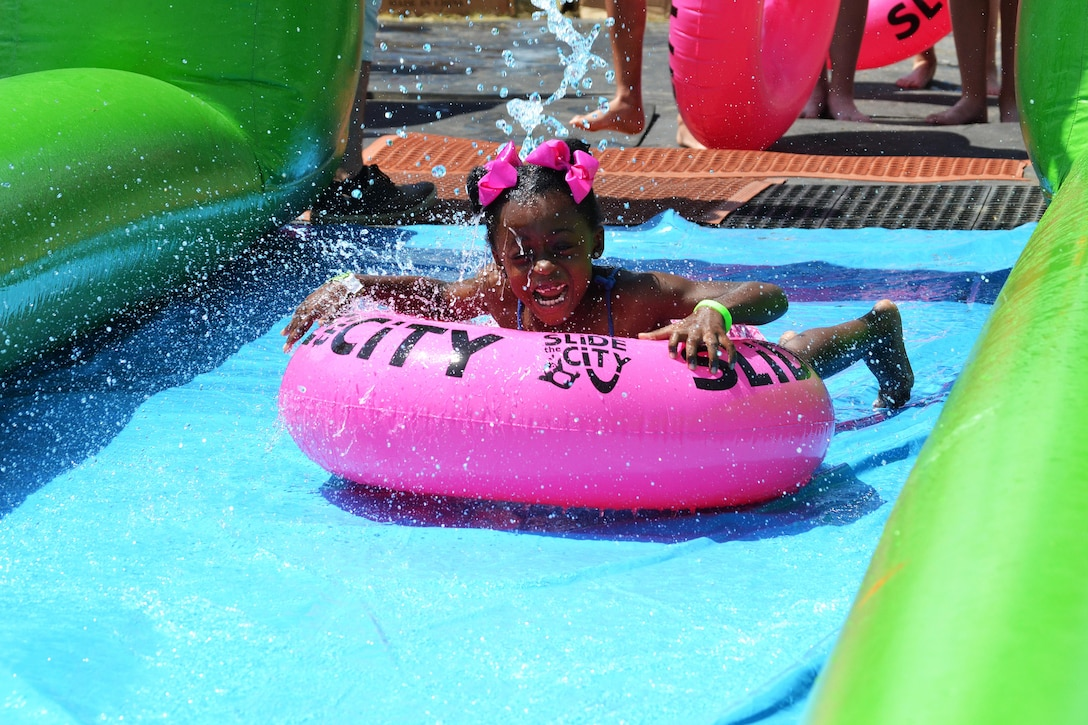 Jasmine Ray slides under a water spout during Slide the City at Schriever Air Force Base, Colorado, Friday, Aug. 19, 2016. Ray was one of the hundreds of Schriever School Age Care and Ellicott School District students who participated in the event. (U.S. Air Force photo/Brian Hagberg)