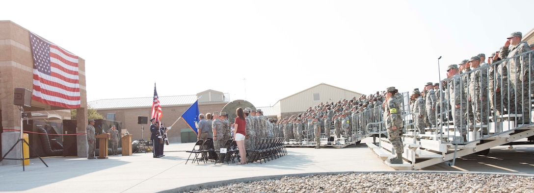 Participants of the 726th Air Control Squadron ribbon cutting ceremony honor the flag as Staff Sgt. Khaiel-Matthew Kuhn-Natividad, 726th ACS interface control technician, sings the national anthem August 18, 2016, at Mountain Home Air Force Base, Idaho. The ceremony was to celebrate the recent renovations to the 726th ACS compound. (U.S. Air Force photo by Airman Alaysia Berry/Released)
