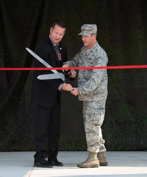 Col. David Gaedecke, 552nd Air Control Wing commander, and Rich Sykes, Mayor of Mountain Home, Idaho cut the ribbon at the 726th Air Control Squadron ribbon cutting ceremony for their new compound August 18, 2016, at Mountain Home Air Force Base, Idaho. The new equipment will allow the 726th ACS to train the way they fight by providing identical equipment to what they deploy with. (U.S. Air Force photo by Airman Alaysia Berry/Released)
