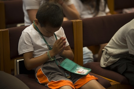 A child prays before getting released to eat during Vacation Bible School at the Marine Memorial Chapel on Marine Corp Air Station Iwakuni, Japan, Aug. 17, 2016. VBS consisted of group discussions, feeding the children and volunteers, praying and rotation stations. (U.S. Marine Corps photo by Lance Cpl. Joseph Abrego)