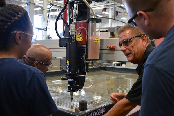 Mr. Ray Williams, 2nd from right, instructs Hull Maintenance Technician Fireman Mionna Green (L-R), Mr. Richard Cornwell and Hull Maintenance Technician 1st Class James Hampton on the intricacies of the cutting head. The cutter uses a 60,000 psi jet of water mixed with fine particles of garnet to cut steel and virtually any other material. Photo by Scott Curtis