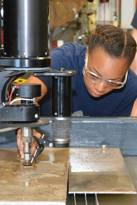 Hull Maintenance Technician Fireman Mionna Green adjusts the clearance of the cutting head on the new waterjet fabrication system at Southeast Regional Maintenance Center. Abrasive waterjet technologies enable the shipfitter shop here to cut components faster and more accurately, delivering them to the fleet more quickly and lowering overall production costs.
