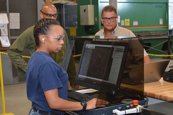 Hull Maintenance Technician Fireman Mionna Green controls the new waterjet fabrication system at Southeast Regional Maintenance Center as Mr. Richard Cornwell and Mr. Ray Williams observe. Abrasive waterjet technologies enable the shipfitter shop here to cut components faster and more accurately, delivering them to the fleet more quickly and lowering overall production costs.
