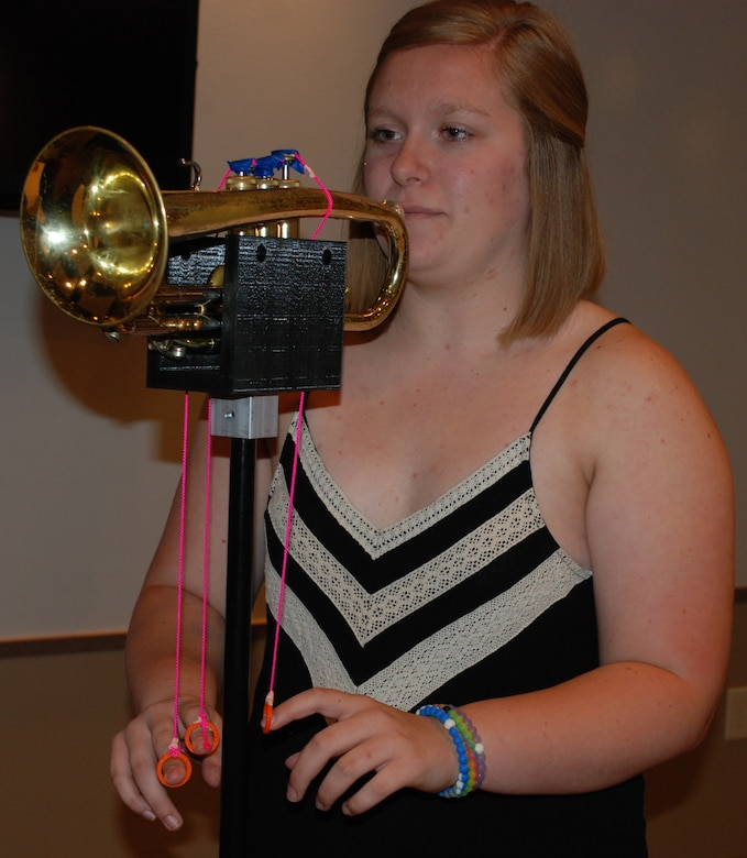 Kirsten Harmon, a recent graduate from Bradford High School, demonstrates how the 3-D printed mounting device will hold the trumpet as well as how the student will be able to pull the strings to move the keys. Harmon and fellow classmate Rachel Lavey collaborated with WBI and the 711th Human Performance Wing to create the stand for a Bradford Middle School student with limited range of motion. (U.S. Air Force photo by Gina Marie Giardina)
